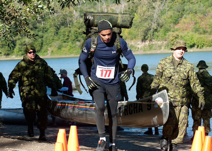 """EN2013-0133 - 33 11 September 2014 Edmonton River Valley Parks Competitor from Exercise Mountain Man finishes the canoe paddle portion of the race at Capilano Park and starts the final stage to the finish line. Exercise Mountain Man took place on September 11th, 2014 in Edmonton's River Valley Parks. The 50 Kilometers competition consisted of a rucksack march, canoe portage, and a canoe paddle, The intent of this military competition is to challenge the limits of soldiers mental and physical toughness within 1 Canadian Mechanized Brigade Group. Photograph by Robert Schwartz, 3 CDSG Edmonton Copyright Notice"""" © 2014 DND-MDN Canada"""