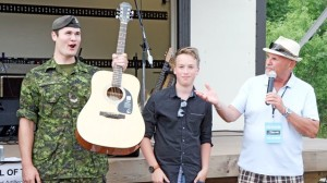 Bombardier Nolan Templeman, left, of the 56th Field Regiment was excited to receive his new instrument from the Guitars for Vets program at Saturday's Blues for Soldiers concert. He accepted it from musician Spencer MacKenzie and Bruce Hall of the Grand River Blues Society.