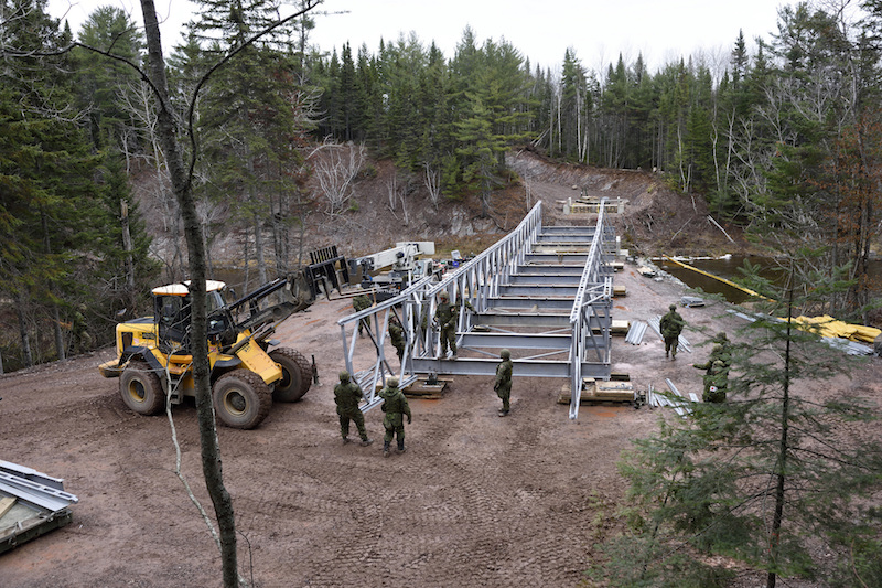 Members of 4 Engineer Support Regiment, continue the construction of the ACROW bridge spanning the Tetagouche River outside Bathurst New Brunswick as another section hangs out over the 149 foot spance to reach the 3/4 way point on 8 November 2016 during Exercise Nihilo Sapper 16. LH01-2016-025-060 Photo by WO Jerry Kean/5 Cdn Div HQ Public Affairs