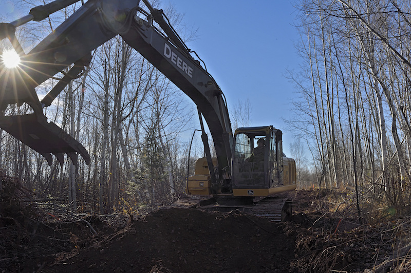 Corporal Will Morgan-Boudreau, Heavy Equipment Troop with 4 Engineer Support Regiment uses an excavator with a claw to clear stumps while clearing brush and trees from a proposed ATV and snowmobile trail outside Bathurst New Brunswick on 7 November 2016 during Exercise Nihilo Sapper 16. LH01-2016-025-048 Photo by WO Jerry Kean/5 Cdn Div HQ Public Affairs